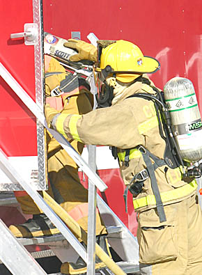 "Firemen enter ""live burn"" trailer for interior attack training."