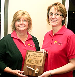Retiring Chamber President Lori Krohn presents the president's plaque to 2013 President Shelley Lueken.