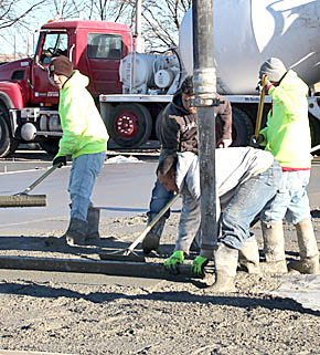 Workers finish concrete floor at the Cardinal Inn motel construction site.