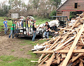 Local crew piles up debris on the Slama farm near Wakefield.
