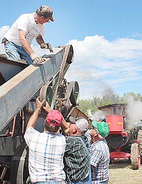 Crew makes some adjustments to the antique threshing machine powered by a steam tractor (background).