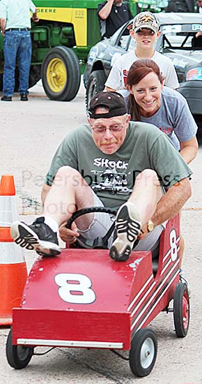 Fire Chief Boomer Baumgartner takes a ride in the derby car with his wife, Julie, pushing.