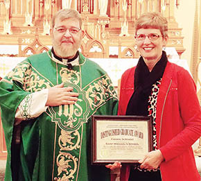 Connie Schindel receives the St. Michael's Distinguished Graduate plaque from Rev. Stan Schmit at St. Michael's Church.