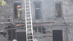 Firemen extinguish hot spots in the home destroyed by fire early Friday morning.