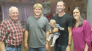 Hank Thieman, l., congratulates new owners of the Knotty Pine (l.-r.) Drew Niewohner, and Justin and Betsy Niewohner. Justin is holding their daughter, Julia, seven months old.