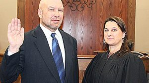 Alan Rasmussen takes the oath of office from Lisa Langan, court clerk/magistrate.