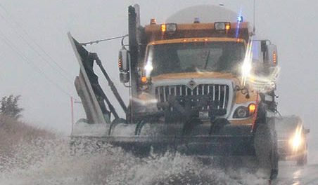Snow plow clears ice and water along Highway 91 east of Albion Monday morning.