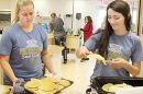 Jaclyn Frey, l., and Jessica Weeder serve up pancakes during the FFA Breakfast last Sunday.