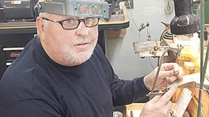 Heartland Jewelry owner Dan Willis repairing jewelry at the Albion store.