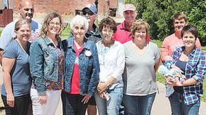 Family members on hand with Donna Merten (third from left) at the Memorial Day flag raising in her honor included (front, l.-r.) Michelle Merten, Brea Kelley, Cindy Carlson, Lori Merten and Taylor Johnston (with baby Everette Johnston); and (back row) Terry Merten, Victor Carlson, Randy Merten and Jonathon Merten.