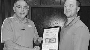 Petersburg Community Club President Jim Leifeld presents Jordan Anderson (right), owner of JRK Electric, with a First Dollar Plaque.