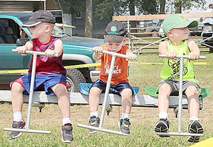 Three boys in John Deere hats ride the old-fashioned merry-go-round during the Rae Valley show.