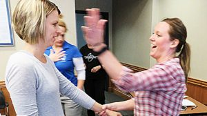 Nicole Levander, l., and Jenni DeWitt practice self-defense moves in slow motion.