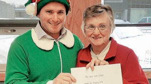 Elves are making the rounds in Albion, presenting Chamber Bucks and business gift certificates to lucky shoppers. Above, Keir Dane Harner presents an envelope to Connie Paulson of Albion.